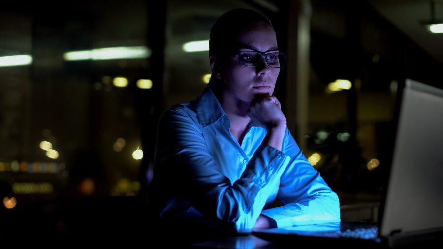 Female working extra hours at night in the office.
