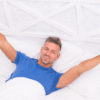 Man waking up in bed looking happy and refreshed.