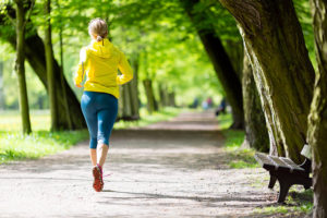 Woman running along path in a park